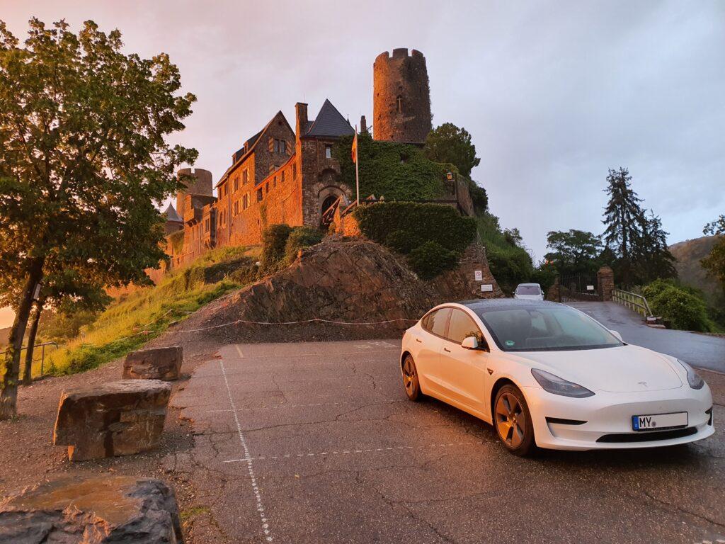 Leichter Regen und letzte Sonne auf dem Tesla Model 3 an der Burg Thurant in Alken/Mosel